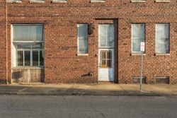 Side of a vintage red brick warehouse with white door in small midwestern town on clear day