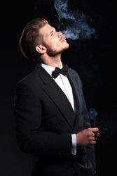 side of an elegant man enjoying his cigar on dark studio background
