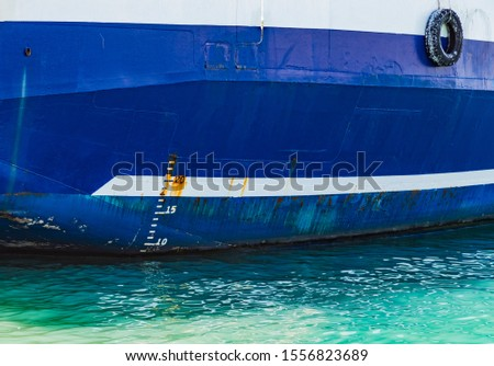 Side of blue cargo ship hull with white waterline and numbers of rough draft scale. International load line, Plimsoll line or water line #1556823689