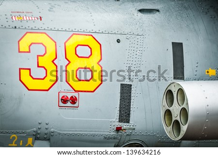 Side of helicopter with red and yellow drawn number 38 and text with russian letters on it. Close-up of military air transport with missile. Army chopper with rockets. Air forces of Russia.