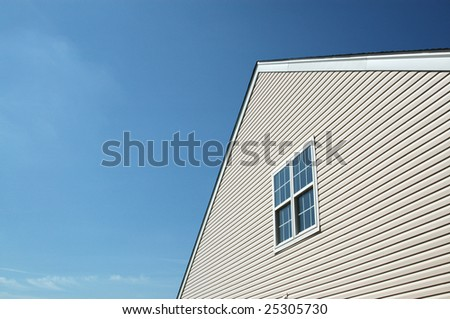 Side of new house showing peaked roof and blue sky. Pair of double-hung windows.