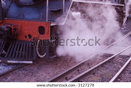 Side of old vintage steam train with steam and smoke in shunting yard