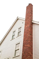 Side of older style white house with tall red brick chimney