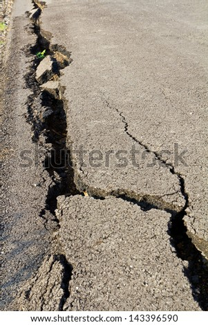 Side of the asphalt road surface crack due to ground collapsing.