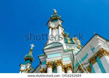 Side of the St Andrew's Church, Kiev, Ukraine. The church is small and painted blue and white, with many decorations on it's facade. Picture taken from under the church. Clear and blue sky