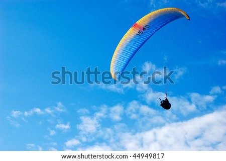 Side paraglider on blue sky with feather clouds