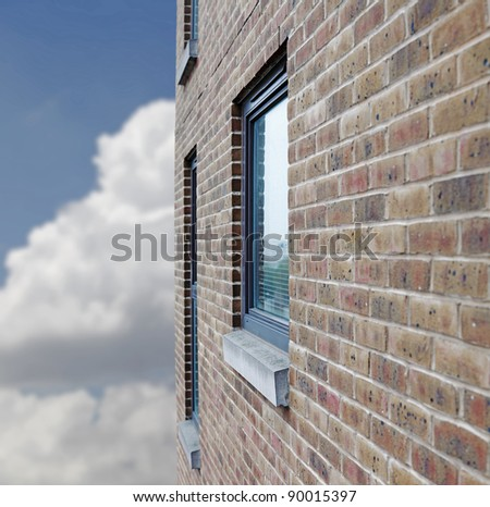 Side perspective of a glass window on a rustic brick wall against a cloudy blue sky.