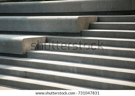 Side perspective on a modern design concrete stairway with inset benches in stadium style seating, in afternoon sunlight