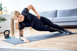 Side plank exercise. Athletic woman doing core workout at home