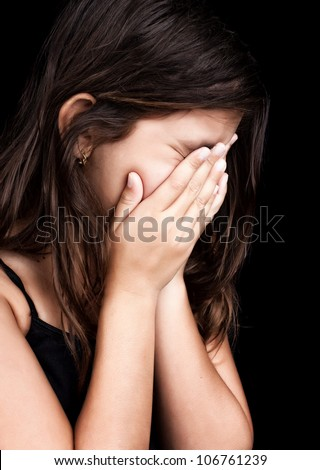 Side portrait of a beautiful girl crying and covering her face isolated on black