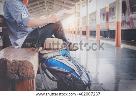 Shutterstock Side portrait of a  young man traveler sitting with map choose where to travel and bag waiting for train at train station, vintage tone filter effected