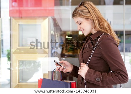 Side portrait of a young teenager tourist visiting the city and carrying paper shopping bags while leaning on a fashion store window, using her smartphone device and smiling.