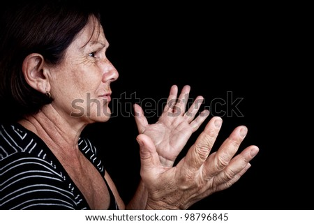 Side portrait of an old woman talking  and gesturing with her hands isolated on black