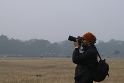 Side portrait of an young Indian Bengali man in winter jacket and taking photograph of sky and trees by his camera in a field in foggy winter morning in green background. Indian lifestyle and winter.