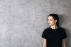 Side portrait of attractive caucasian girl in black shirt on textured concrete background with copy space