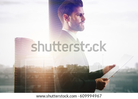 Side portrait of attractive thoughtful businessman on city bakcground with sunlight. Double exposure