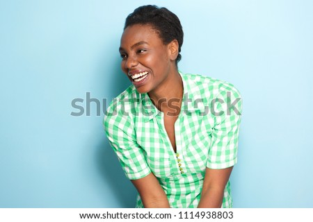 Side portrait of beautiful african american woman laughing by blue wall #1114938803
