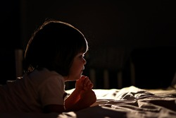 Side portrait of cute little child praying on bed in dark bedroom with backlight. Bedtime. Low key, backlit. Profile silhouette