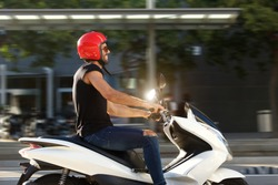 Side portrait of handsome smiling man on motorcycle ride in city