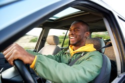 Side portrait of happy african american man driving car