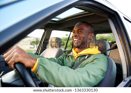 Side portrait of happy african american man driving car #1363330130