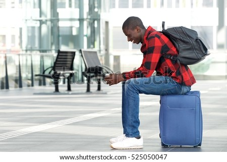 Side portrait of happy young man sitting on traveling bag and looking at cell phone