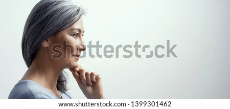 Side Portrait Of Smiling Asian Woman With Grey Hair Touching The Chin. Beautiful Middle-Aged Woman In Profile Touching Chin