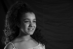 Side portrait of smiling teenage girl without looking at the camera with black background and curly hair. Black and white horizontal image. Concept of emotions.