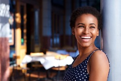 Side portrait of smiling young black woman standing outside