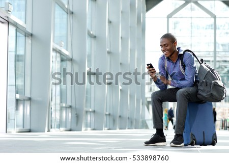 Side portrait of smiling young businessman sitting on suitcase looking at phone #533898760
