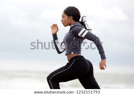 Side portrait of sporty young black woman running #1232151793