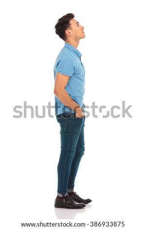 side portrait of young man in blue shirt looking up with hands in pockets while posing in isolated studio background #386933875