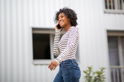 Side portrait smiling young african american woman walking and talking with mobile phone outside