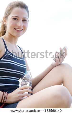 """Side portrait view of a young attractive woman having a break from exercising and holding a bottle of mineral water and a """"smart phone"""", smiling."""