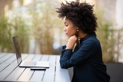 Side portrait young african american business woman sitting with laptop computer