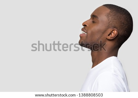 Side profile african male standing on grey background aside copyspace for your advertisement text. Positive american guy closed eyes enjoy fresh air make deep breath, dreaming feels peaceful concept