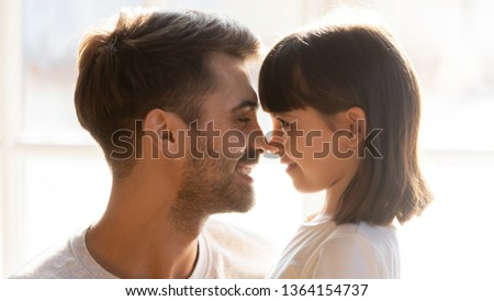 Side profile close up smiling faces, loving father adorable daughter looking at each other touching noses expressing love sincere feelings, connection and warm relationship between dad and kid concept