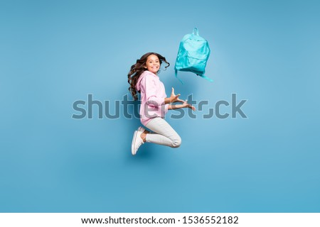 Side profile full length body size photo of cheerful pink positive preteen schoolchild catching her backpack wearing pants trousers footwear isolated pastel blue color background Foto stock ©