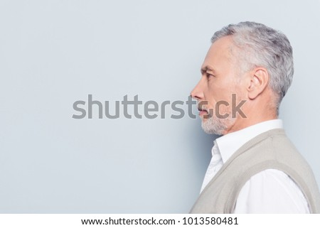 Side profile half-faced portrait of pensive thoughtful serious concentrated confident qualified experienced grandpa knitted waistcoat white shirt isolated on gray background copyspace