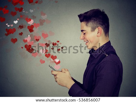 Side profile happy man sending love sms text message on mobile phone with red hearts flying away from screen isolated on gray wall background. Positive human emotions #536856007