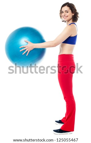 Side profile of a fit woman holding an exercise ball in her outstretched arms.