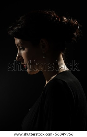 Side profile of a young woman on a dark background