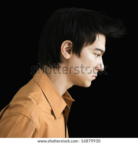Side profile of serious Asian young man.