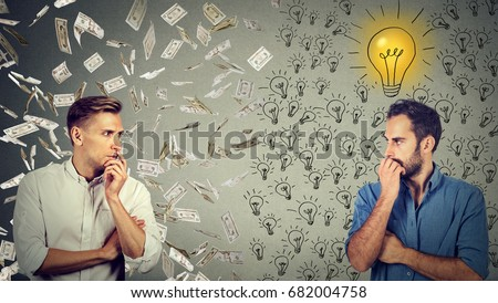 Side profile of two serious businessmen looking at each other one under money rain another with bright ideas #682004758