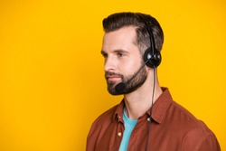 Side profile photo portrait of confident call center assistant worker in headphones microphone isolated on vibrant yellow color background