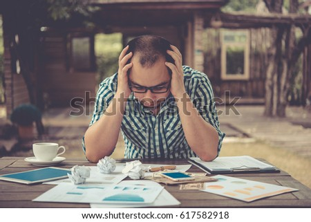 Side profile stressed young businessman sitting outside corporate office holding head with hands looking down. Negative human emotion facial expression feelings.