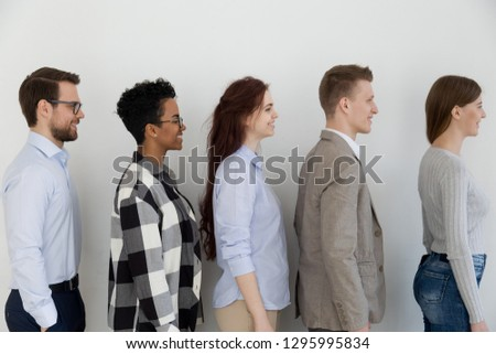 Side profile view at happy diverse business people standing in queue, smiling multi ethnic applicants seekers waiting for job interview or casting in line row along wall, human resources concept