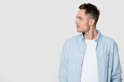 Side profile view of man looking at empty copy space. Studio photoshoot of stylish male turning head aside watching to blank gray background. Advertisement banner, editable promotion, sale concept