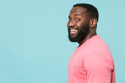 Side profile view of smiling young african american man 20s in casual pink t-shirt looking camera isolated on pastel blue wall background studio portrait. People lifestyle concept. Mock up copy space