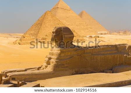 Side profile view of the Great Sphinx with all of the pyramids of Giza in the background in Cairo, Egypt on a clear sunny, blue sky day. Horizontal
